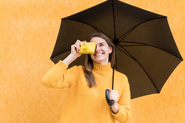 Mujer sosteniendo un paraguas negro y una cámara amarilla