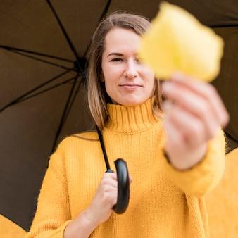 Mujer sosteniendo un paraguas negro y una hoja amarilla