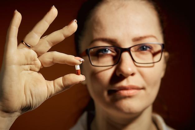 Mujer sosteniendo una pastilla en su mano, tratamiento de resfriados.