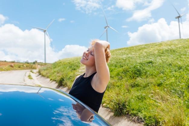 Mujer sosteniendo el pelo y disfrutando del sol por la ventana del coche