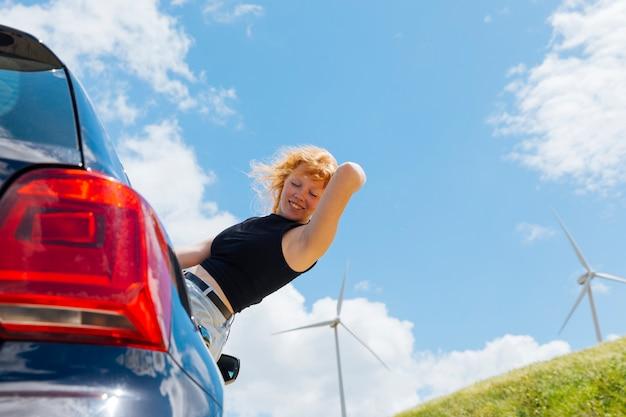 Mujer sosteniendo el pelo y mirando hacia abajo por la ventana del coche