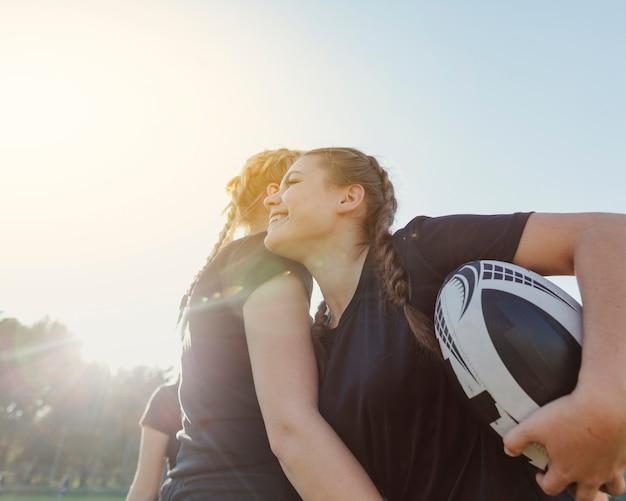 Mujer sosteniendo una pelota y abrazando a su compañero de equipo