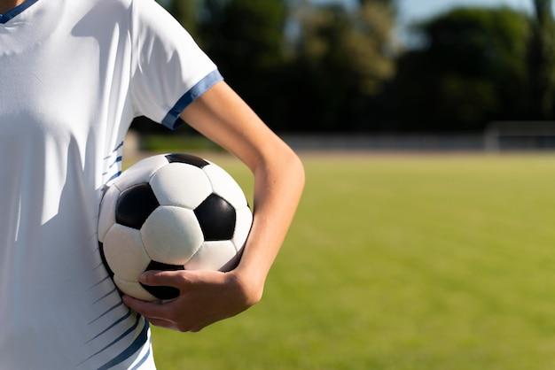 Mujer sosteniendo una pelota de fútbol en el campo