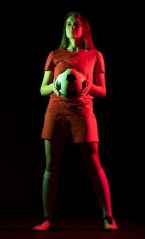 Mujer sosteniendo una pelota de fútbol