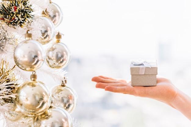 Mujer sosteniendo una pequeña caja de regalo en la mano