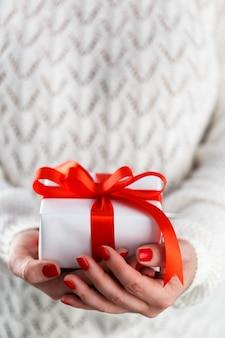 Mujer sosteniendo pequeña caja de regalo roja