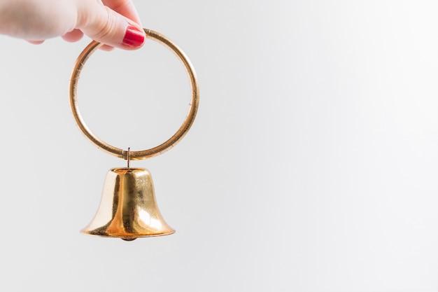 Mujer sosteniendo pequeña campana en la mano