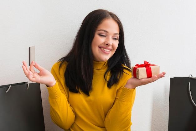 Mujer sosteniendo un pequeño paquete de regalo