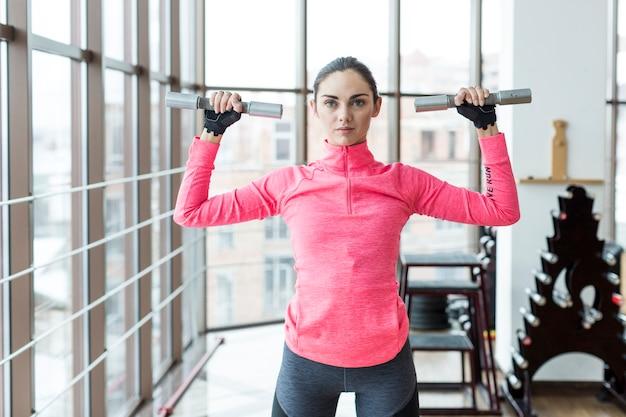 Mujer sosteniendo pesas con las manos en alto