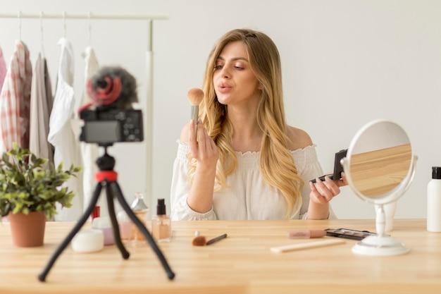 Mujer sosteniendo pincel de maquillaje