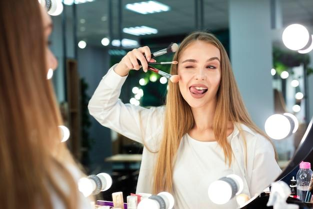 Mujer sosteniendo pinceles de maquillaje haciendo cara graciosa