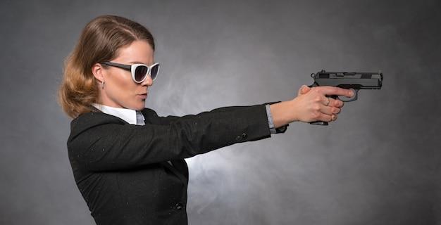 Mujer sosteniendo la pistola con ambas manos y apuntando al objetivo