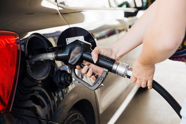 Mujer sosteniendo la pistola de llenado en las manos y alimentando el coche