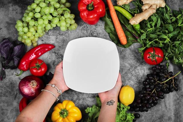 Mujer sosteniendo plato blanco sobre fondo de mármol con verduras frescas.