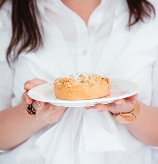 Mujer sosteniendo un plato con tarta de manzana