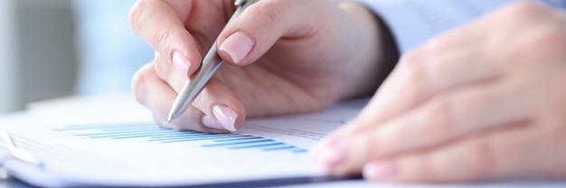 Mujer sosteniendo la pluma en sus manos y estudiando gráficos en documentos closeup