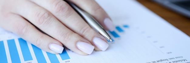Mujer sosteniendo la pluma en sus manos sobre documentos con gráficos closeup