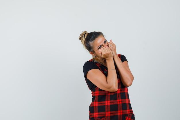 Mujer sosteniendo los puños en la cara con vestido delantal y mirando molesto. vista frontal.
