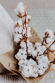Mujer sosteniendo un ramo de flores de algodón