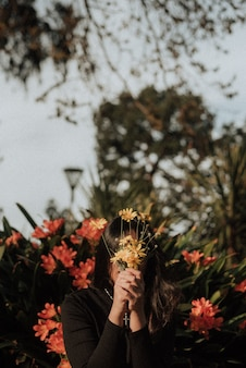 Mujer sosteniendo un ramo de flores silvestres en frente de su cara en un jardín con un fondo natural
