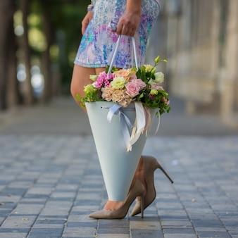 Mujer sosteniendo un ramo de flores en la vista de la calle