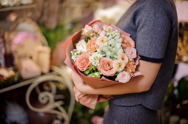 Mujer sosteniendo un ramo de rosas beige y otras flores blancas