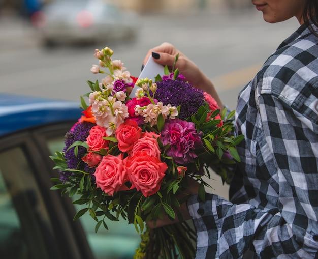 Una mujer sosteniendo un ramo de rosas coloridas y tomando la tarjeta de felicitación en la mano en la calle