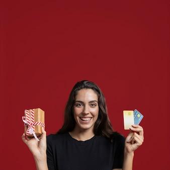 Mujer sosteniendo un regalo envuelto y sus tarjetas de crédito