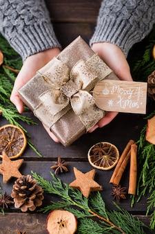 Mujer sosteniendo regalos de navidad sobre un fondo de mesa de madera.