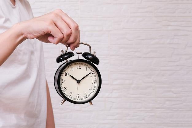 Mujer sosteniendo un reloj despertador que muestra las 10 en punto, la gente debe valorar y apreciar el tiempo, espacio de copia del concepto de fecha límite