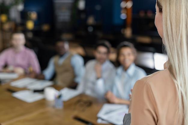 Mujer sosteniendo una reunión de oficina con compañeros de trabajo