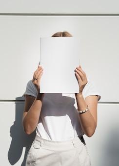 Mujer sosteniendo revista maqueta