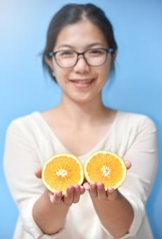 Mujer sosteniendo rodajas de naranja.