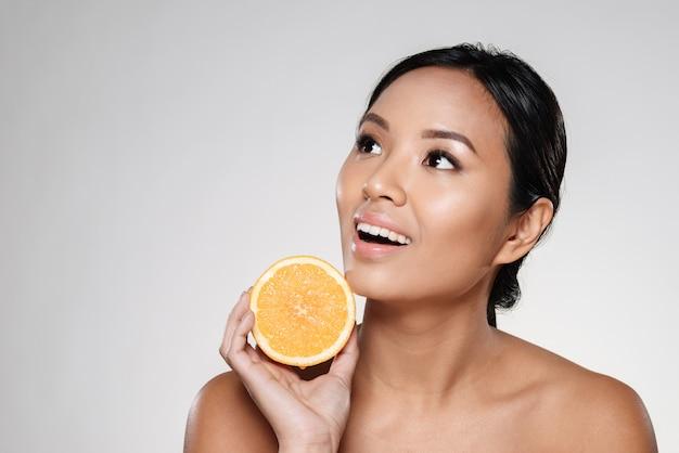 Mujer sosteniendo rodajas de naranja cerca de su cara