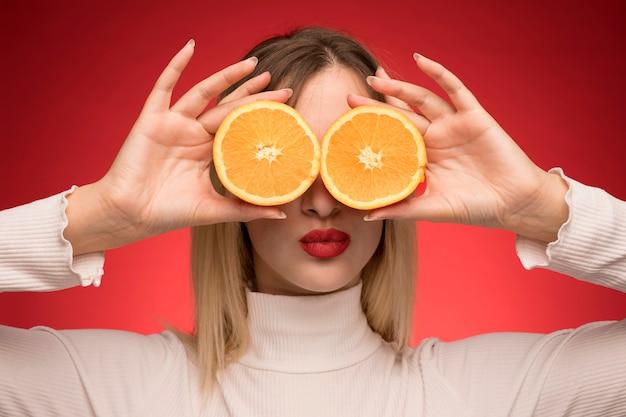 Mujer sosteniendo rodajas de naranja sobre sus ojos