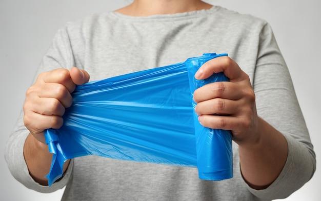 Mujer sosteniendo un rollo de bolsas de basura azul en su mano