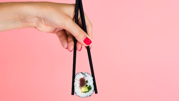 Mujer sosteniendo un rollo de sushi sobre un fondo rosa