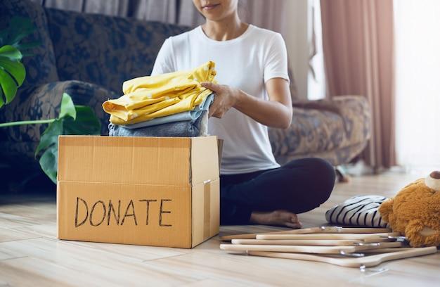 Mujer sosteniendo ropa con caja de donar en su habitación