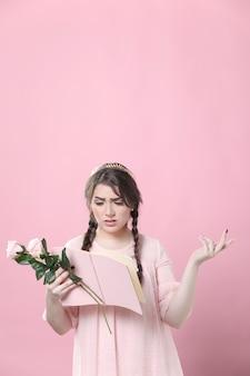 Mujer sosteniendo rosas sin entender el libro que está leyendo
