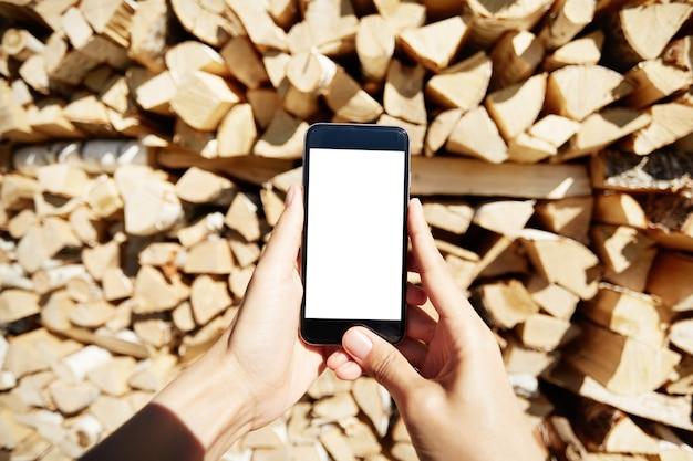 Mujer sosteniendo smartphone con pantalla en blanco en blanco