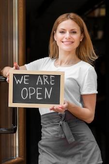 Mujer sosteniendo somos señal abierta