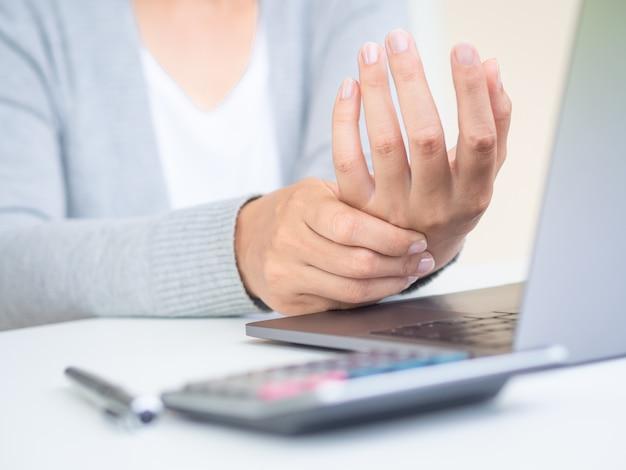 Mujer sosteniendo su dolor de mano por usar la computadora por mucho tiempo