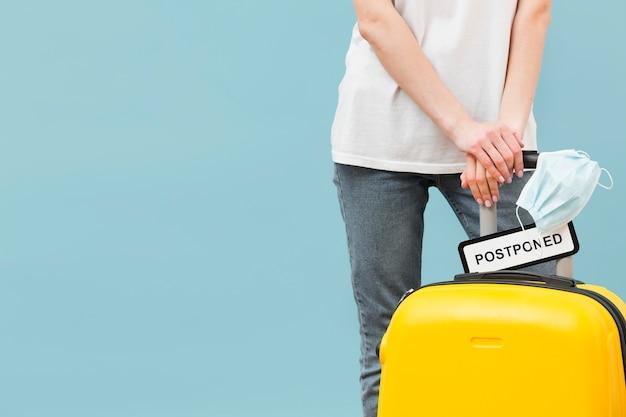 Mujer sosteniendo su equipaje con un cartel pospuesto con espacio de copia