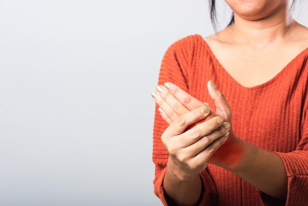 Mujer sosteniendo su muñeca de manos