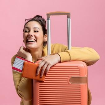 Mujer sosteniendo su pasaporte y equipaje