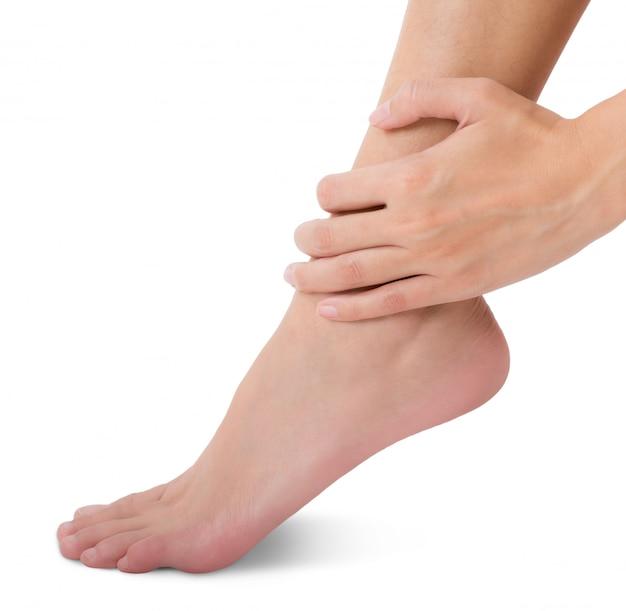 Mujer sosteniendo su pie y masaje tobillo en el área del dolor aislado en blanco