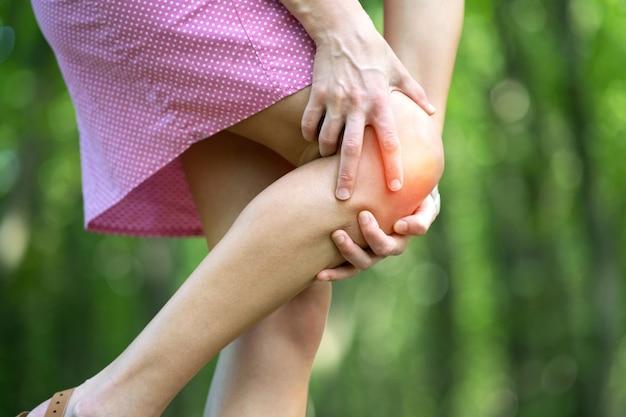 Mujer sosteniendo su rodilla con las manos con fuerte dolor.