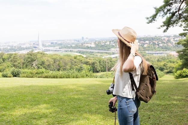 Mujer sosteniendo su sombrero y mirando a otro lado