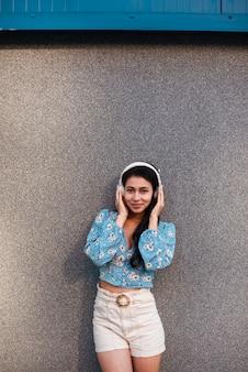 Mujer sosteniendo sus auriculares y mirando a cámara