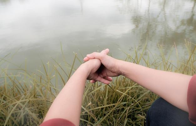 Una mujer sosteniendo sus manos en el río.